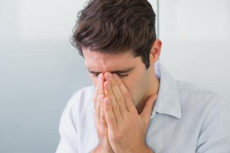 desolaci�n: Close up de un hombre joven ocasional triste con las manos a la cara en el hogar