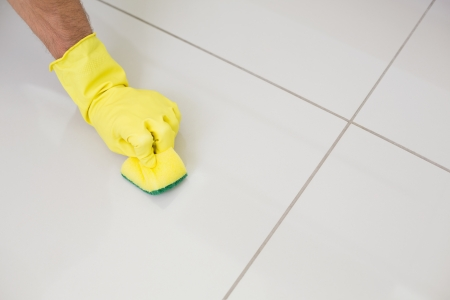 Close up of yellow gloved hand with sponge cleaning the floor at home photo