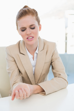 Young businesswoman suffering from wrist pain in the office photo
