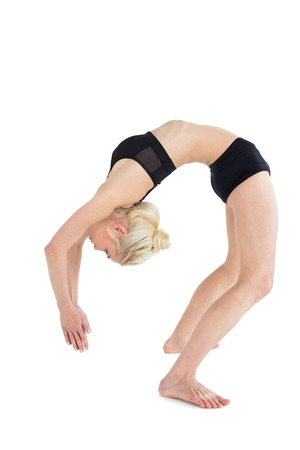 Full length side view of a fit young woman bending backwards over white background Stock Photo