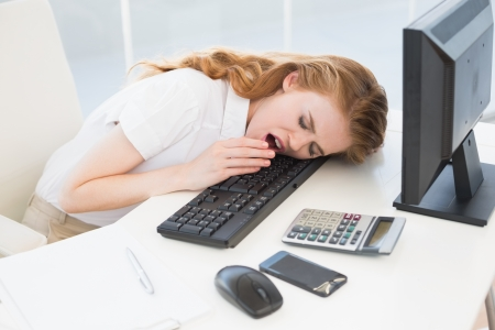 Young businesswoman resting head on keyboard while yawning in the office photo