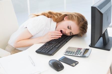 Giovane donna di affari che riposa la testa sulla tastiera mentre si sbadiglia in ufficio