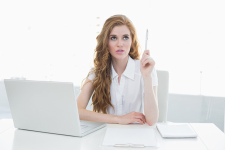 Beautiful young businesswoman with laptop pointing upwards at desk in a bright office photo