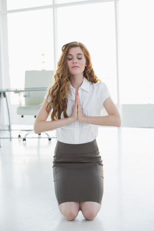 Worried elegant businesswoman kneeling with joined hands in a bright office photo
