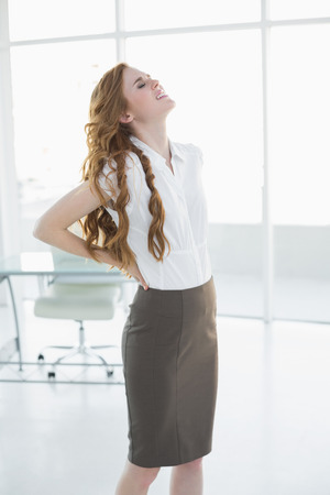 classy woman: Young elegant businesswoman suffering from back ache in a bright office