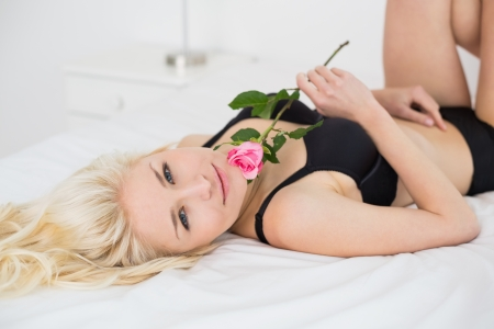 Portrait of a beautiful young woman lying in black lingerie with rose on bed photo