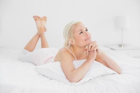 joined hands: Relajado mujer muy joven con las manos juntas acostado en la cama en su casa