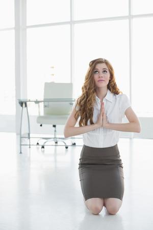 joined hands: Preocupado elegante empresaria de rodillas con las manos unidas en una oficina brillante