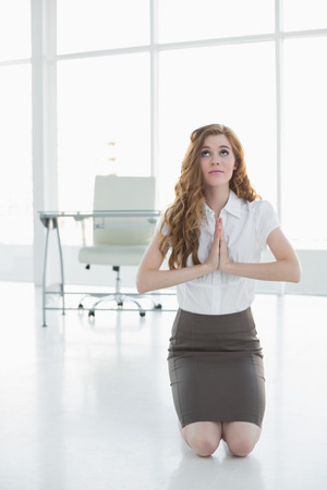 Worried elegant businesswoman kneeling with joined hands in a bright office