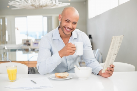 Portrait of a smiling young man drinking coffee while reading newspaper at home photo