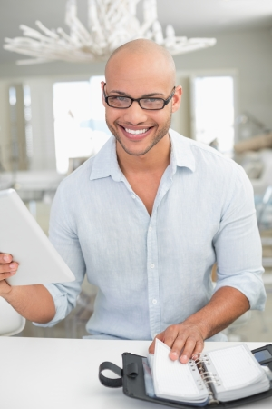 Portrait of a casual smiling young man with digital tablet and diary at home photo