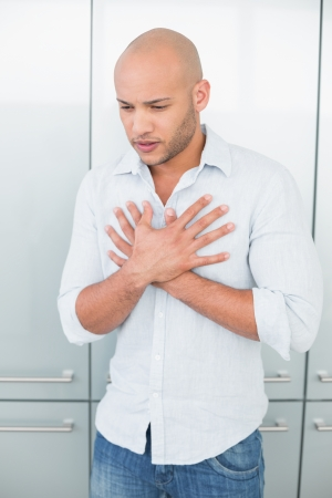 Casual young man with chest pain standing against wardrobe at home photo