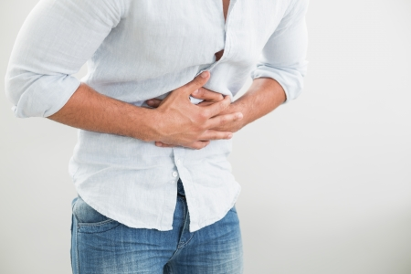 Close up mid section of a young man suffering from stomach pain against white background