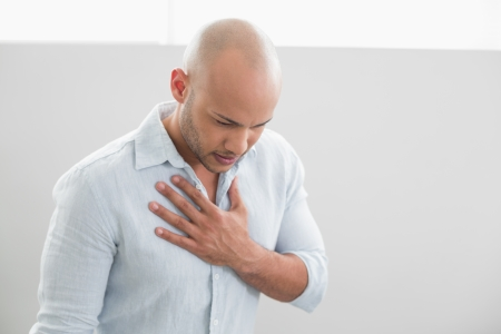 Casual young man with chest pain standing against white background photo