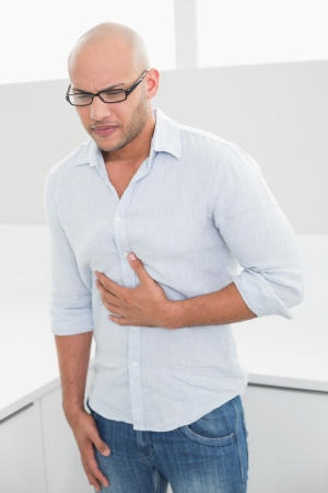 Casual young man suffering from chest pain standing at home photo