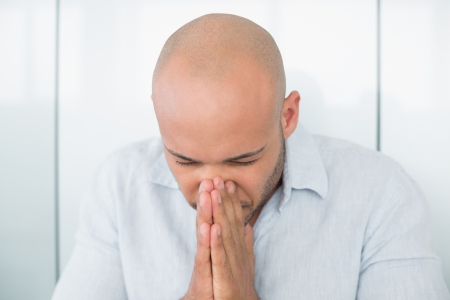 Close up of a sad casual young man with hands to his face at home