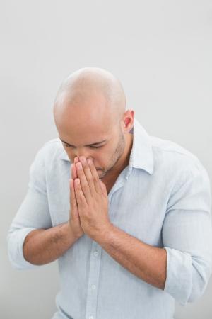 desolaci�n: Primer plano de un hombre joven ocasional triste con las manos a la cara contra el fondo blanco Foto de archivo