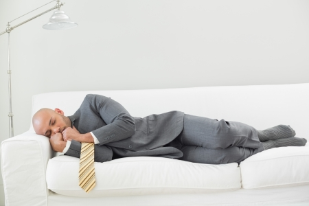 Full length of an elegant businessman sleeping on sofa at home