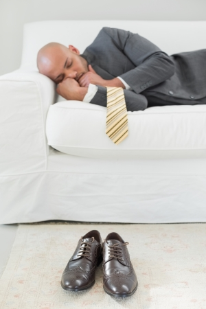 Elegant young businessman sleeping on sofa at home photo