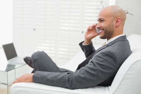 Side view of a smiling elegant young businessman using cellphone on sofa at home photo