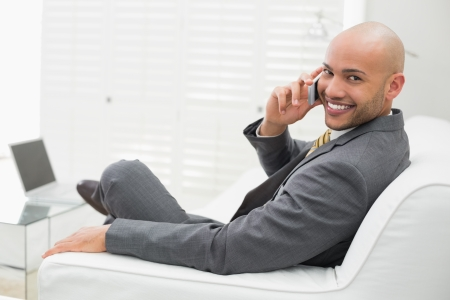 Side view portrait of a smiling elegant young businessman using cellphone on sofa at home photo