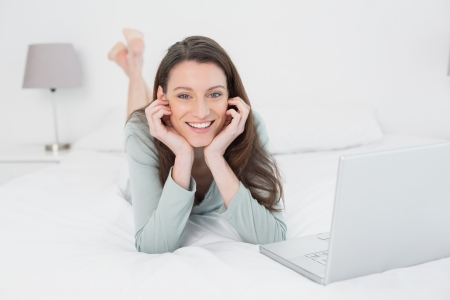 Portrait of a relaxed casual smiling young woman with laptop in bed at home photo