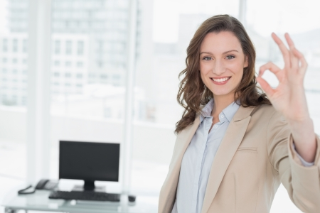 Portrait of an elegant smiling businesswoman gesturing okay sign in a bright office photo