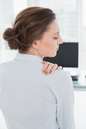 Rear view of a businesswoman with neck pain in front of computer in a bright office photo