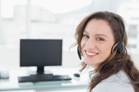 Portrait of businesswoman wearing headset in front of computer in a bright office