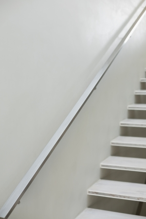 hand rails: Close up of stairs and hand rails along white wall Stock Photo