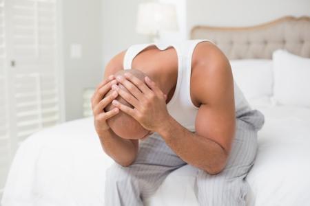 bald man: Hombre calvo joven pensativo sentado con la cabeza en las manos sobre la cama en su casa Foto de archivo