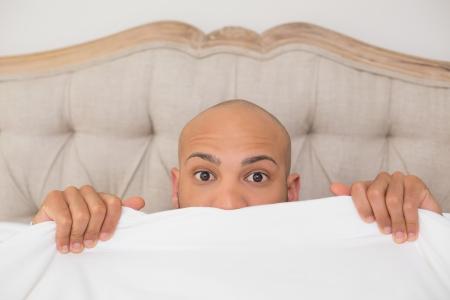 brown eyes: Cerrar un retrato de un hombre calvo sorprendida joven que cubre la cara con la hoja en la cama en su casa Foto de archivo