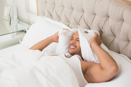 Young sleepy man covering ears with pillow in bed at home photo