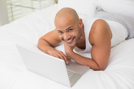 Portrait of a smiling casual bald young man using laptop in bed at home photo