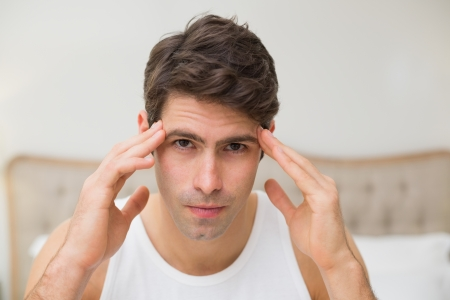 pounding head: Close up of a young man suffering from headache in bed at home Stock Photo