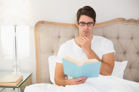 Relaxed young man reading book in bed at house photo