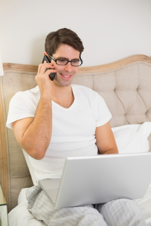 Casual smiling young man using cellphone and laptop in bed at home photo