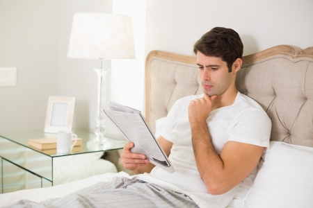Casual young man reading newspaper in bed at home photo