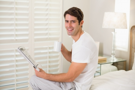 Portrait of a smiling man with coffee cup reading newspaper in bed photo