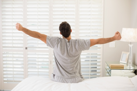 Rear view of a young man waking up in bed and stretching his arms Reklamní fotografie