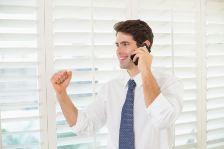 Smiling young businessman using mobile phone while clenching fist in office