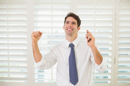 Cheerful young businessman with mobile phone clenching fist in office photo