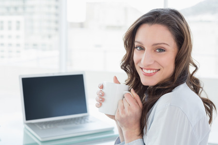 Portrait of a smiling businesswoman with coffee cup in front of laptop in a bright office photo