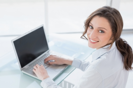 Portrait of a smiling brown haired businesswoman using laptop in a bright office photo