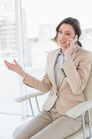 Smiling elegant businesswoman using mobile phone in a bright office photo