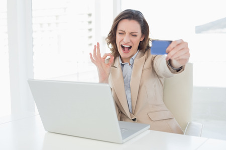 Businesswoman doing online shopping through laptop and credit card in office photo