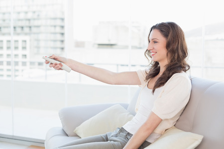 changing channels: Side view of a smiling young woman with remote control sitting on sofa at bright home