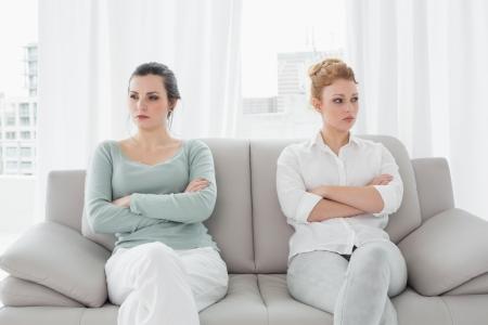 not talking: Infelice giovane amiche non parlare dopo l'argomento a casa sul divano Archivio Fotografico