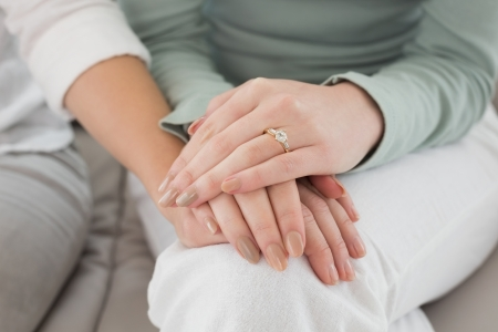 Close-up mid section of female friends touching hands at home
