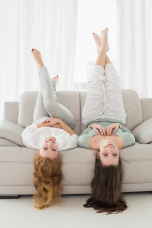 Portrait of two smiling young female friends lying on sofa with legs in the air in living room at home photo